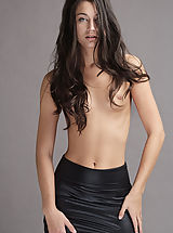 X-Art Pics: 18 year old Georgia sheds her sleek black leather miniskirt and poses nude gazing into the camera with emerald green eyes.